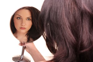 Beautiful Brunette Looking In Mirror On White