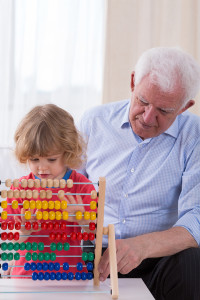 Patient loving granddad learning grandson math on abacus