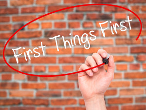 Man Hand writing First Things First with black marker on visual screen. Business, technology, internet concept.