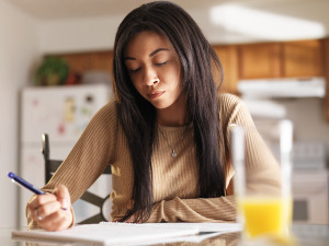 close up of african american teen girl studying in kitchen with breakfast