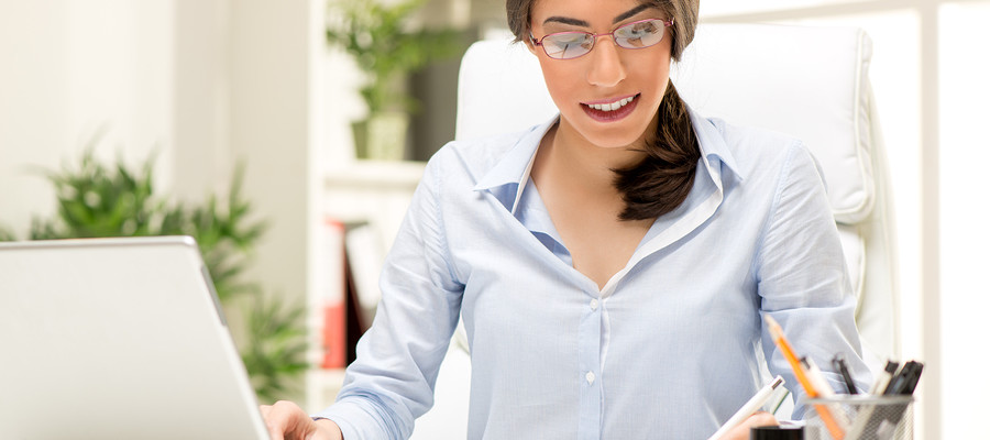 A young beautiful businesswoman sitting at an office desk in front of a laptop and writing in planner with the left hand.