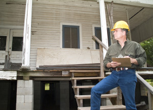 A man in a hard hat holding a clipboard standing on the steps of an old rundown house.