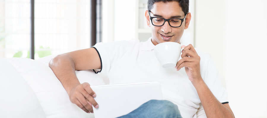 Indian guy drinking a cup of coffee while using digital pc tablet at home. Asian man relaxed and sitting on sofa indoor. Handsome male model.