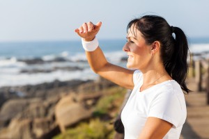 fit mature woman looking into distance at beach in the morning